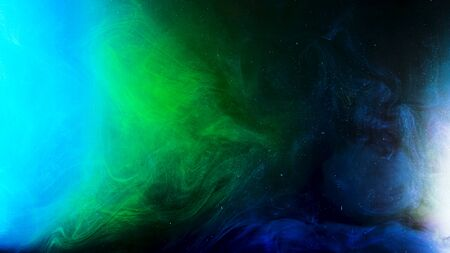 Fantastic view of colorful inks in chaotic motion on black background with glowing particles. Green and blue paints in liquid texture, art concept. 版權商用圖片