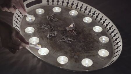 Magic ritual of burning paper with candles. Close up of divinations before Christmas, women hands burning small pieces of paper on the metal tray, traditions and superstitions concept. Banque d'images