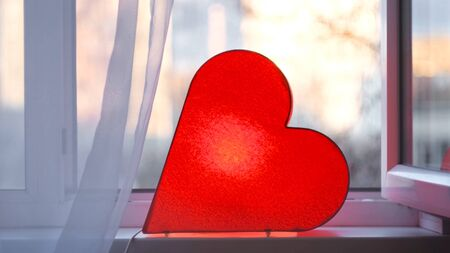 Bright lamp in shape of heart is on window. Concept. Red heart-shaped lamp stands at window and glows to bestow love on everyone. Bright romantic decor.