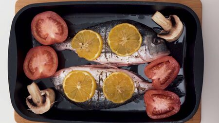 Top view of process of cooking fish. Close up of raw fish being cut, salted and spicied, ant then grilled with mushrooms, tomatoes and slices of orange, healthy food concept.