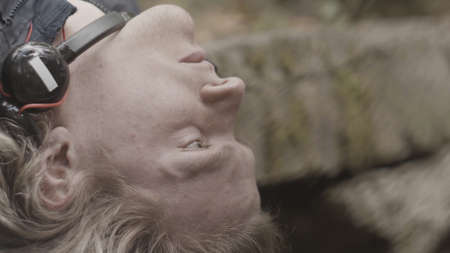 Close up of a blond man face with closed eyes. Stock footage. Caucasian man with his head thrown back lying outdoors with headphones on his neck and looking sad and pensive.