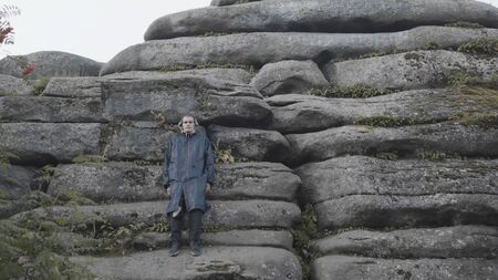 A man stands near a stone rock. Stock footage. Front view of a young male in long coat and headphones leaning on giant stones of a mountain, concept of travel. Фото со стока