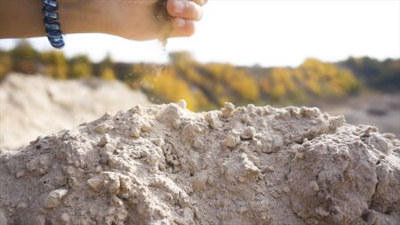 Close up of dry soil in a hand of a woman. Stock footage. Female hand with a blue plastic scrunchie on her wrist blowing dried soil in the wind on green blurred forest background. Banque d'images