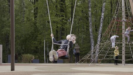 Little child blond girl having fun on a swing outdoors at children playground. Stock footage. Concept of childhood and leasure, lovely child playing on swing set.