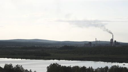 Natural landscape of a river, green forest, mountains and old factory with a smoking chimney. Air pollution and smoke from the plant on cloudy sky background.