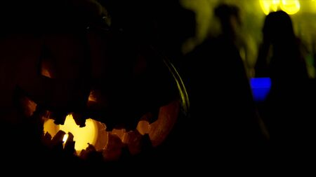 Close up of pumpkin on a table for Halloween. Stock footage. Scary pumpkin at the night club with people silhouettes at the bar counter on the background. Imagens