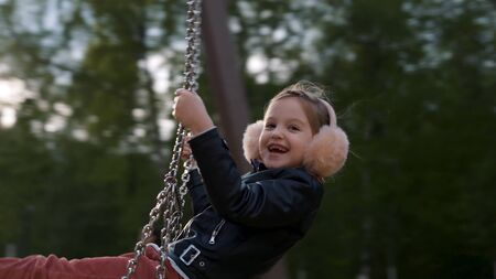Little child blond girl having fun outdoors on children playground. Stock footage. Beautiful blond caucasian girl smiling while walking in the street.