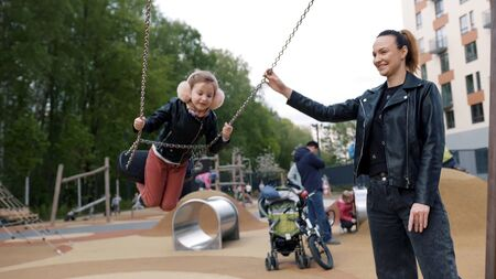 Portrait of little daughter and mother playing swing in the park while smiling together. Stock footage. Mother pushing her daughter on a swing at outdoor playground, family concept.
