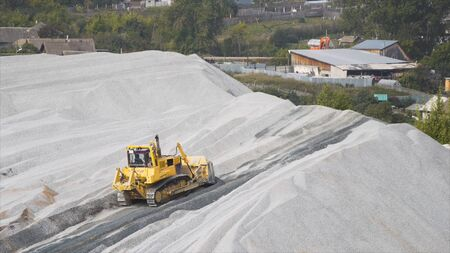Bulldozer spreading rubble on a stone quarry. Stock footage. Yellow construction tractor working on the quarry and spreading gravel near the village.