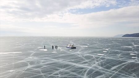 Group of people standing on cracked stnning ice lake near hovercraft. Clip. People travel and explore the frozen Baikal Lake in a safe and comfortable hovercraft. Imagens