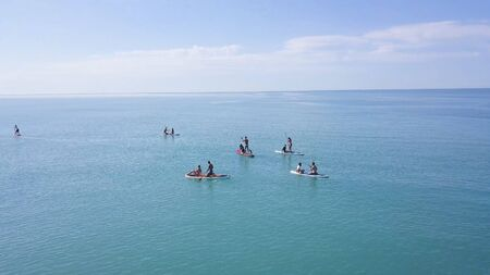 Group of people swim on SUP Board. Clip. Beautiful seascape with people resting on water with SUP boards. Top view of turquoise sea with people on swimming boards