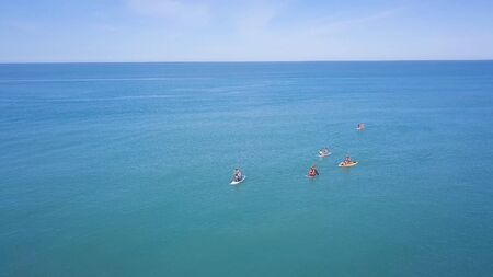 Top view of tourists on sea with SUP-boards. Clip. Beautiful clear sea with people floating on boards engaged in sup-surfing. Seascape with people rowing on boards on background horizon