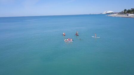 Top view of tourists on sea with SUP-boards. Clip. Beautiful clear sea with people floating on boards engaged in sup-surfing. Seascape with people rowing on boards on background horizon. Imagens