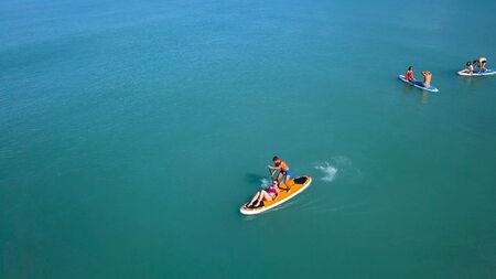 Couple floating on board with paddle. Clip. Top view of couple of vacationers during sea trip on SUP-Board. Seascape with couple engaged in sup-surfing Imagens