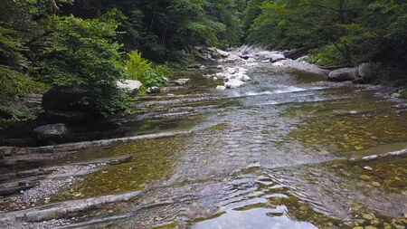 Beautiful mountain river flowing through green forest. Clip. Clear low river runs along mountain ledges on background of green lush forest