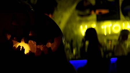 Halloween spooky pumpkins in the dark bar. Close up of scary pampkin with a yellow lamp inside and people having fun on the background.