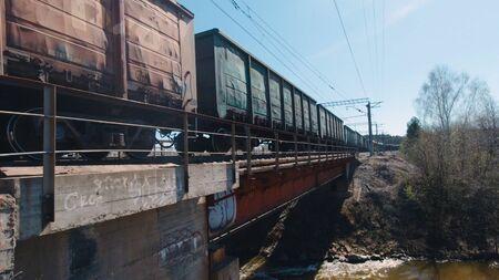 Running train on old bridge over river. Clip. Freight train passing over old bridge over muddy river in spring. Path of freight train over bridge. 版權商用圖片