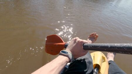 Man on raft paddles in river. Clip. First-person view of quiet muddy river rafting in spring. Quiet single river rafting on sunny day. 版權商用圖片