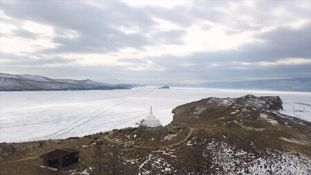 Buddhist stupa on the island of Ogoy on Baikal lake. Clip. Culture and traditions of Siberia, white stupa on frozen water of Baikal on the background, place of divine enlightenment.
