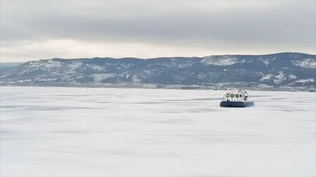 Hovercraft on the ice of lake Baikal in winter time. Clip. Aerial view of the air cushion vehicle on the thick ice of the frozen lake, sports transport and extreme concept. Stock Photo