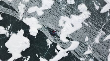 Aerial top view of group of people lie on thick transparent ice. Clip. Camera moving towards happy friends lying on the frozen lake in a form of a circle.
