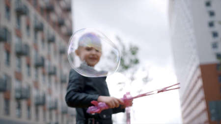 Active little blond girl with a braid blowing bubbles on residential building background. Action. Adorable excited female child playing with soap bubbles at the playground.