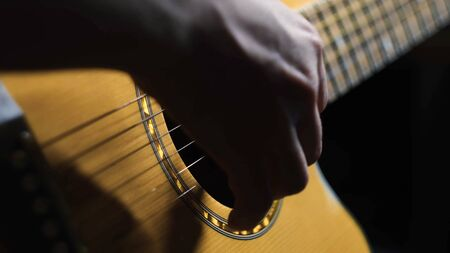 Close-up of man playing guitar. Concept. Professional guitar player moves fingers along strings of guitar beautifully. Atmospheric guitar playing.