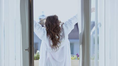Attractive woman stretch on balcony. Video. Back view of beautiful woman in white coat stretching on balcony on sunny morning. Attractive woman on vacation abroad.