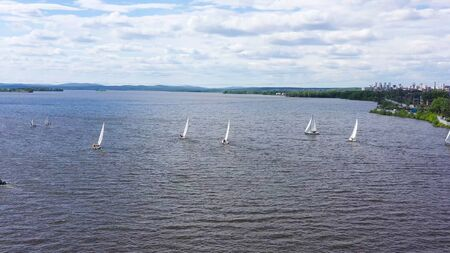 Top view of competition of sailing yachts. Video. Beautiful regattas floating on background of green coast and distant city. Landscape of lake with floating regattas. Stock Photo