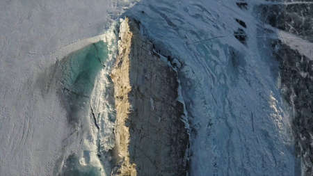 Separate stone cliff near the coast of Lake Baikal, Siberian winter nature. Clip. Aerial view of the rock with steep slopes on the background of the lake under the snow and ice.