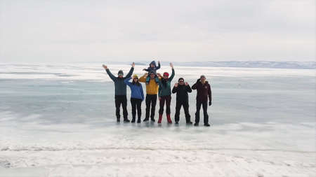 A group of tourists travels along the ice of the frozen Lake Baikal. Clip. Aerial view of happy people waving to the camera while standing on the icy surface, concept of active lifestyle and extreme sport.