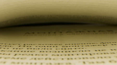 Close up of an open book with a gap between two pages. Stock footage. Camera moving along the printed lines of the page on black background, concept of reading.