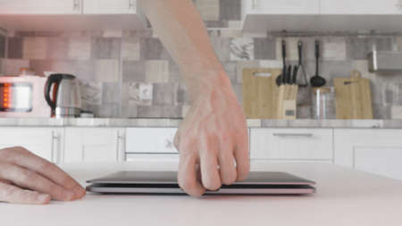 Close up of the modern computer on the kitchen table. Action. Time lapse effect, man is walking at in the kitchen at home and trying to open his silver color laptop.