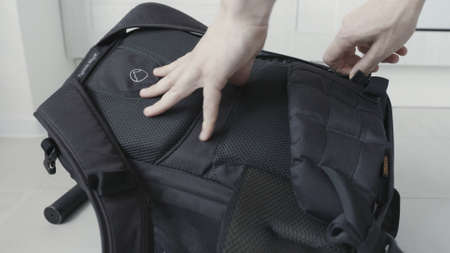 Packing protective soft material for laptop or other devices. Action. Close up of male hands putting black foam rubber layer inside a backpack.