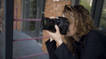 Portrait of female photographer with professional camera. Action. Side view of caucasian woman with curly hair taking pictures on her camera on red brick wall background.