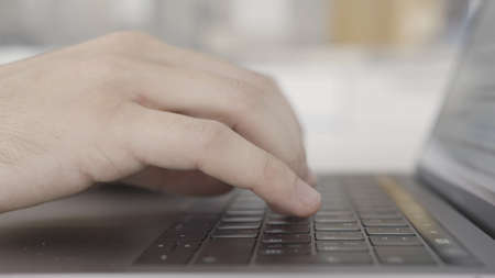 Working at home with laptop, male hands on the keyboard. Action. Close up side view of hands typing on keypad of the computer, concept of modern technologies. Stock Photo