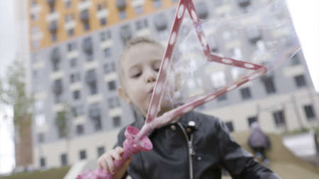 Portrait of a pretty little girl blowing giant bubbles in slow motion. Action. Blond caucasian female girl creating soap bubbles on multistorey building background.