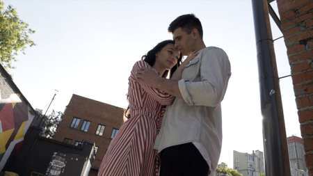 Man and woman in love embracing in the street. Action. Happy caucasian young couple hugging and smiling outdoors against the bright sunlight, bottom view.
