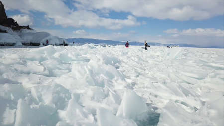 Lake Baikal, beautiful blue thick ice with cracks on a sunny day. Tourists explore wild breathtaking russian nature in winter season, concept of extreme travelling.