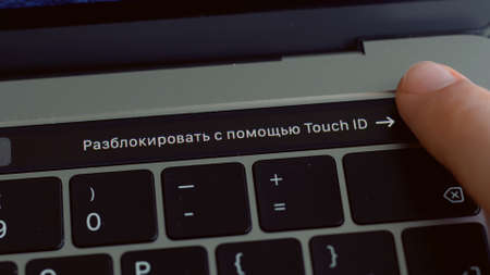 Close up of a finger unblocking modern laptop with touch id technology. Action. Using male fingerprint to activate system of macbook, computer technologies concept.