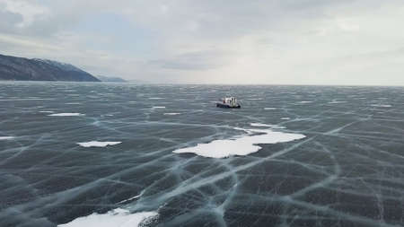 Snow air motion boat goes on big snow field of a frozen lake. Clip. Aerial view of icy surface of the Baikal lake near cliffs of Olkhon Island.
