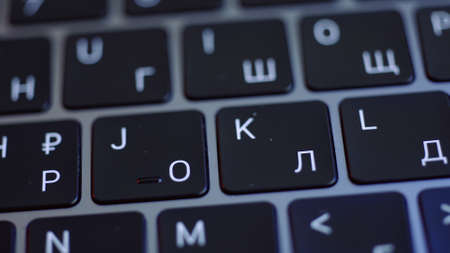 Close up of the keyboard of a laptop in black and white colors. Action. Concept of modern computer technologies, laptop keypad with glowing letters.