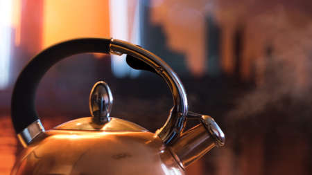A metal silver teapot on a gas stove in the kitchen at home. Concept. Close up of steel kettle with boiling water, preparation of hot beverage.