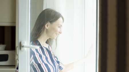 Dark haired smiling woman opens the door of a balcony and looks outside. Video. Side view of a happy lady at home looking outdoors through a window of a living room on a sunny day.