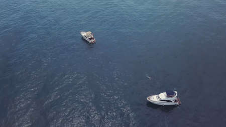 Top view of sailing boats and a man swimming in the open sea. Video. Amazing aerial view of two white yachts in deep blue sea in front of the endless horizon.