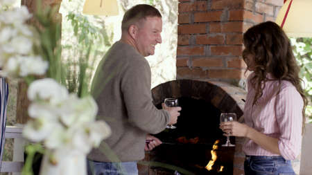 Man and woman drink wine, talking and smiling inside the cottage. Video. Side view of a couple of man and woman chating and flurting while man roasting meat in the fireplace during the barbeque party.