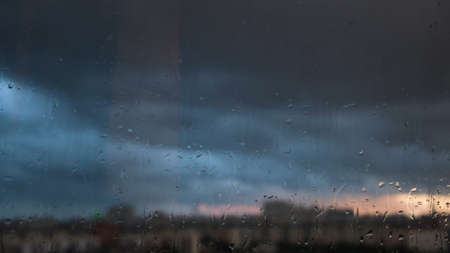 Rain drops on window with peaceful evening or night city background behind. Concept. Water drops on wet glass with blurred sky and houses during rain.