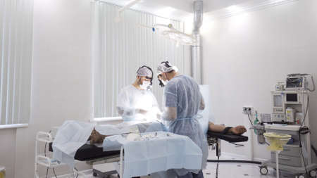 Team of doctors perform surgery while patient is under anesthesia. Action. View inside of the operating room with men surgeons and sedated male patient. 写真素材