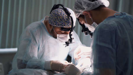 Medical team performing operation. Action. Close up of faces of surgeons at work wearing binocular loupes in operating theatre during the procedure.