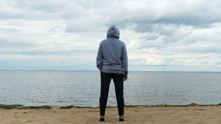 Back view of a male at the Gulf of Finland, Saint Petersburg, Russia. Concept. Rear view of a man in sports clothes standing on the beach and looking far away in the distance.
